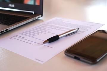 Bild wird vergrößert: Neben dem Laptop liegen ein Handy und ein Blatt Papier mit Text, darauf ein Stift.