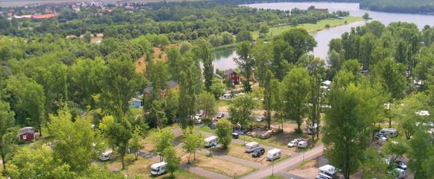 Wohnmobilplatz aus der Luft am Hainer See, viele grüne Bäume und dazwischen vereinzelte Wohnmobile