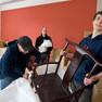 Drei Männer stehen in einem Raum voller unausgepackter Kartons, einer trägt gerade einen Stuhl.