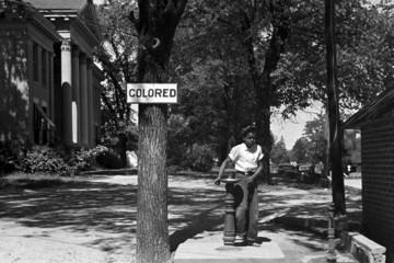 """Bild wird vergrößert: Ein Junge an einer Säule, daneben ein Zettel an einem Baum mit der Aufschrift """"Colored"""""""