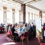 Blick in einen Saal in dem an großen Tischen in kleinen Gruppen sitzend diskutiert wird.