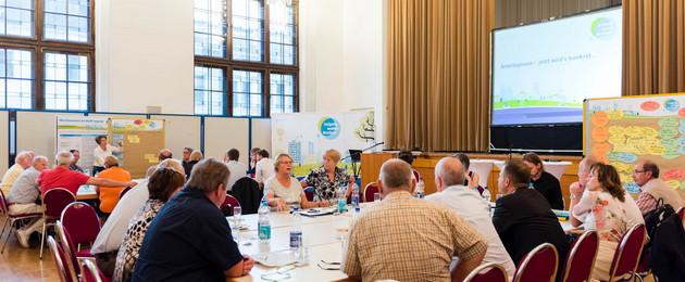 An großen Tischen in einem Sitzungssaal diskutieren Arbeitsgruppen von circa 20 Menschen über den ÖPNV