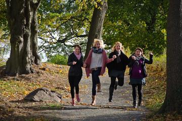 Bild wird vergrößert: Vier Frauen rennen Hand in Hand durch einen Wald.