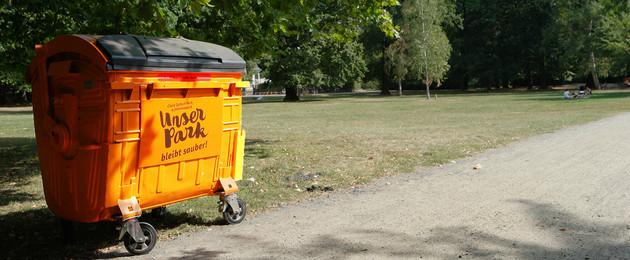 """Vor einer gepflegten und aufgeräumten Parkwiese steht ein großer oranger Müllcontainer mit dem aufgedruckten Logo """"Unser Park""""."""