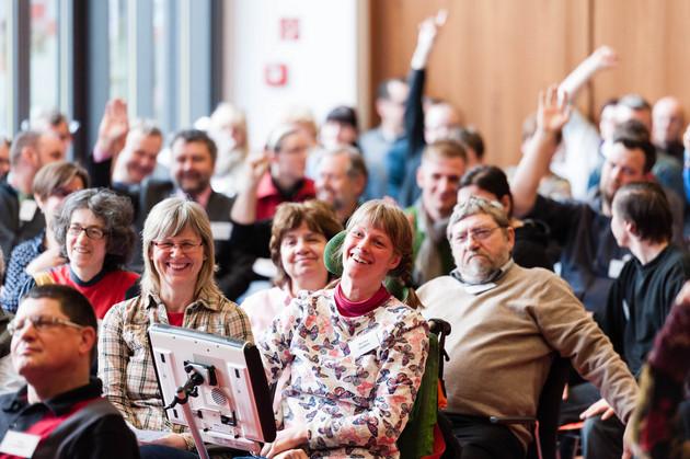 Blick in einen Saal voller Menschen. Einige melden sich. Vorn sitzt eine junge lachende Frau im Rollstuhl mit Sprachcomputer.
