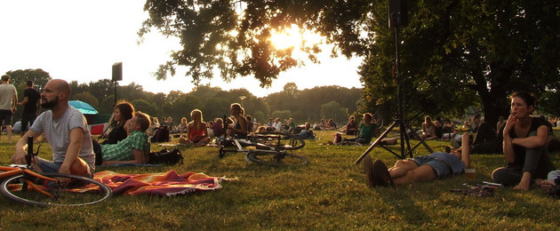 Viele Menschen sitzen in der Abendsonne zwischen Lautsprechern auf einer Wiese.