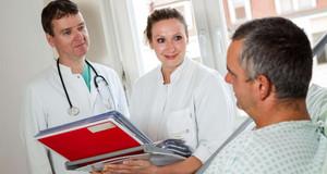 Zwei Ärzte stehen neben einem Patientenbett