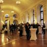 Ein festlich geschmückter Saal in gedimmtes Licht getaucht. Zahlreiche Menschen stehen um Stehtische und unterhalten sich.