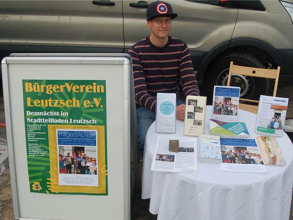 Ein junger Mann sitzt an einem Tisch mit vielen Flyern darauf, daneben steht ein Aufsteller des Bürgervereins.