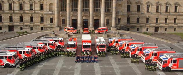 Im Halbkreis aufgestellte Einsatzfahrzeuge von Berufs- und Freiwilliger Feuerwehr nebst Sondertechnik mit davor angetretenen Feuerwehrangehörigen