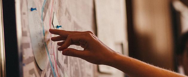 Nahaufnahme einer Hand, die auf eine Pinnwand zeigt