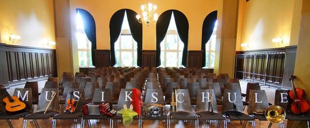 Instrumente sind auf einer Stuhlreihe mit dem Schriftzug Musikschule aufgereiht.