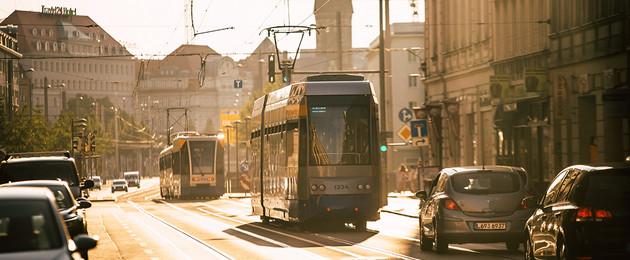 Zwei Straßenbahnen und Autos sind auf der Jahnallee unterwegs.