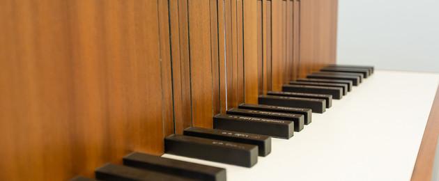 Nahaufnahme der Tastatur eines Klaviers aus braunem Holz