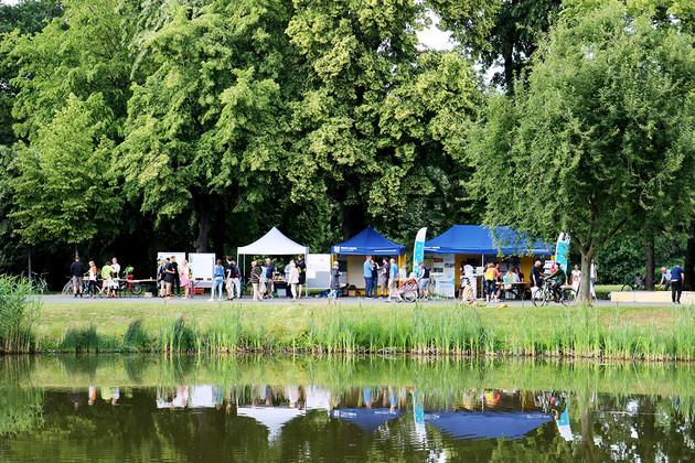 Verschiedene Stände bei der Ökofete im Clara-Zetkin-Park mit einem Teich davor.
