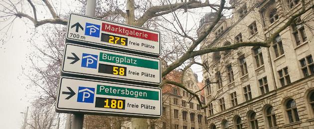 Wegweiser zu verschiedenen Parkhäusern vor dem Neuen Rathaus. Es werden die freien Plätze in den Parkhäusern angezeigt.