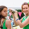 Eine Jugendliche und eine Frau, beide in grünen T-Shirts. Die Frau hält einen Shaker in den Händen.