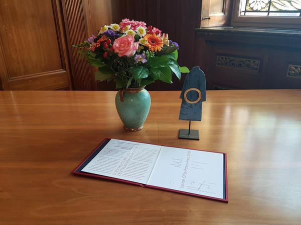 Urkunde, Blumenstrauß und Kunstgegenstand des Louise-Otto-Peters-Preises auf einem Holztisch