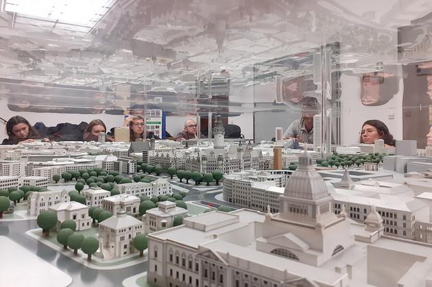 Mehrere Menschen stehen um ein Stadtmodell herum.