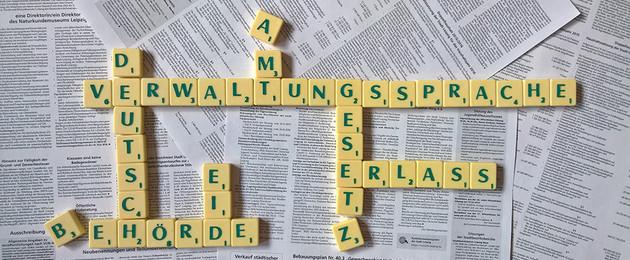 Scrabblebuchstaben liegen auf Bekanntmachungsseiten und formen die Wörter Verwaltungssprache, Deutsch, Bescheid, Amt und Erlass