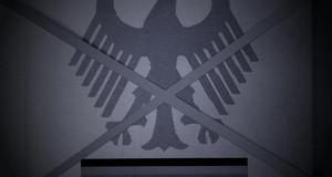 Durchgestrichenes Grundgesetz mit Bundesadler