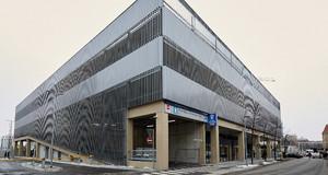 Außenansichtansicht des Fernbusterminals Hauptbahnhof. Funktionales Gebäude mit metallener Außenverkleidung und einer Einfahrt zu einem Parkhaus.