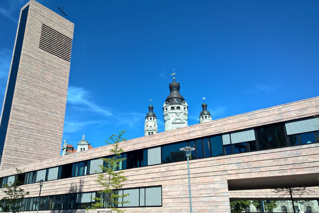 Propsteikirche Leipzig von Eingang Nonnenmühlgasse im Hintergrund Spitzen des Neues-Rathauses im blauen, wolkenlosem Himmel