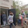 Menschen laufen durch eine Tür in ein Haus hinein.
