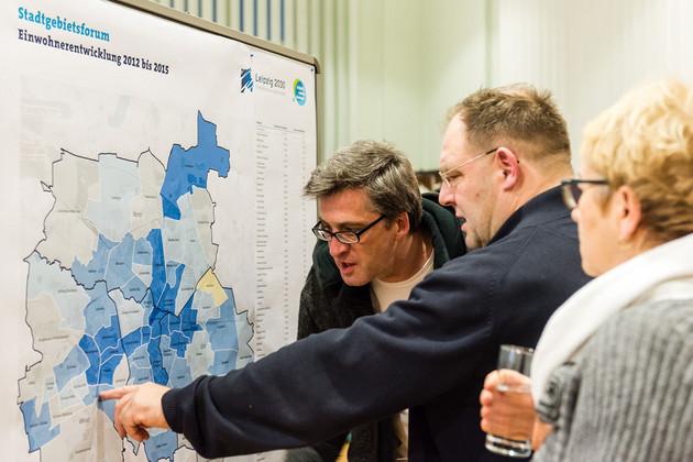 Drei Menschen stehen vor einer Ausstellungstafeln, ein Mann zeigt den anderen etwas auf der Karte