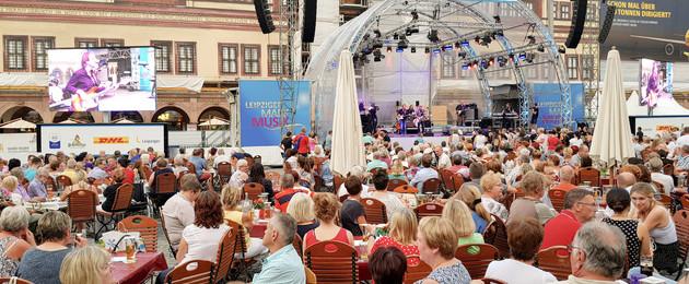 Viele Menschen sitzen auf dem Markt vor dem Alten Rathaus auf Stühlen an Tischen. Sie schauen sich das Konzert an. Auf einer Bühne vor dem Alten Rathaus spielen Musiker.