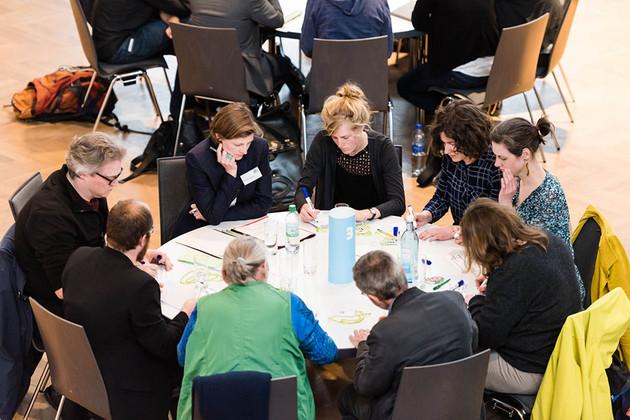 9 Menschen sitzen an einem runden Tisch und schreiben.