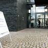 """Vor einem Haus mit einer Fassade aus schwarzen Ziegeln und mit einem großen Glaseingang steht ein Aufsteller mit der Aufschrift """"Teilhabe-Forum, Ich gehör' dazu, 5. März 2015, Medien-Campus Villa Ida""""."""