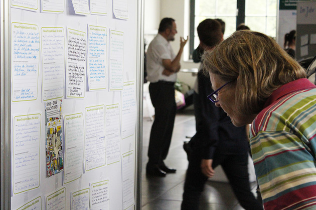 Eine Frau blickt auf die vielen Projektsteckbriefe, die auf einer Säule befestigt sind