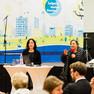 Bürgermeisterin Frau Dubrau begrüßt die Teilnehmenden. Neben ihr steht eine Frau an einem Stehtisch. Im Raum sitzen weitere Menschen.