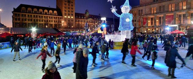 Eisfläche vor der Oper mit vielen Menschen, die eislaufen. In der Mitte steht ein leuchtendes Männchen mit spitzem Hut, das aussieht, als ob es große Schneeflocken aus einem Korb in die Luft wirft.