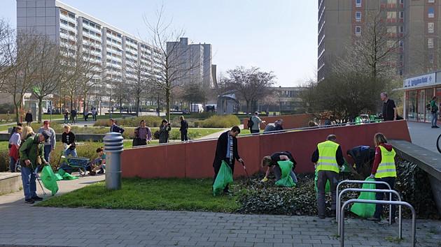 Viele Menschen sammeln Müll in Müllsäcke in der Stuttgarter Allee