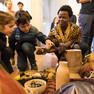 Zwei Kinder, die von einer afrikanischen Frau handgefertigte afrikanische Schalen gezeigt bekommen.