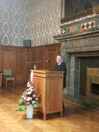 Frau steht hinter einem Rednerpult und spricht zum Publikum