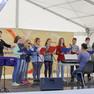 Auf der Bühne singen Schüler Lieder. Sie werden von ihrer Lehrerin am Keyboard begleitet. Die Gebärdensprachdolmetscherin übersetzt den Text.