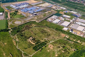 Bild wird vergrößert: Luftbild des Werksgeländes von Porsche in Leipzig mit vielen Werkshallen, einer Testrennstrecke und Grünflächen.