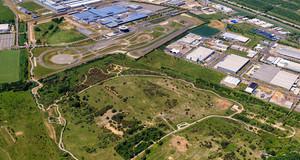 Luftbild des Werksgeländes von Porsche in Leipzig mit vielen Werkshallen, einer Testrennstrecke und Grünflächen.
