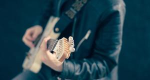 Gitarre, die von einem Menschen gespielt wird.