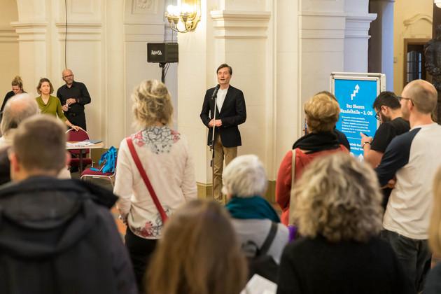 Im Vordergrund sind die Hinterköpfe der Besucher zu sehen, die Heiko Rosenthal bei der Eröffnungsrede zuhören, der im Hintergrund am Mikrofon steht.