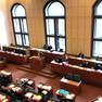 Der Ratsplenarsaal im Neuen Rathaus aus der Vogelperspektive. Zu sehen sind zahlreiche Zuhörer und ein Redner am Pult.