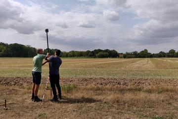 Bild wird vergrößert: Zwei Männer stehen auf einem Feld und justieren ein Messgerät.