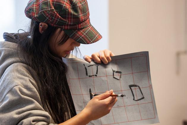 Eine Chinesin hält ein Blatt Papier in die Höhe, auf welches chinesische Schriftarten gezeichnet worden