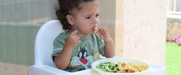 Ein kleines Mädchen sitzt im Hochstuhl und steckt sich eine Pommes in den Mund. Auf dem Tischchen vor ihr steht ein Teller mit Kartoffelstreifen und Gemüse.