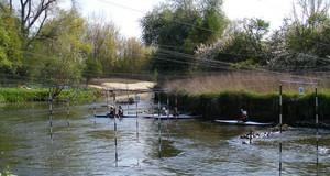 Kanuten auf einer Wasserstrecken mit abgesteckten Wassertoren.