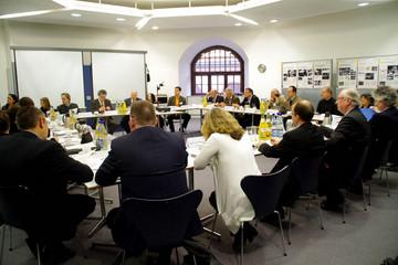 Bild wird vergrößert: Experten sitzen sich in einem Raum an Tischen gegenüber und diskutieren miteinander.