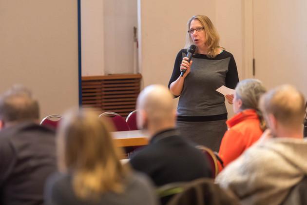 Im Vordergrund sind verschwommen die Zuhörer eines Vortrags im Festsaal zu sehen, im Hintergrund steht Corinne Graf, die Referentin, mit einem Mikrofon in der Hand.